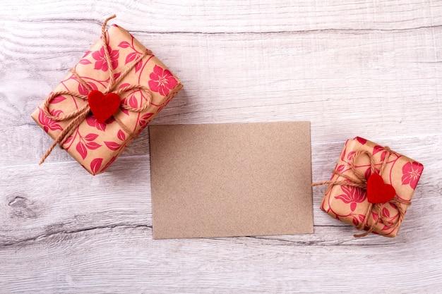 Pezzo di carta e scatole regalo. cuori di stoffa sui regali. divertiti a fare regali. un'idea utile per decorare la scatola.