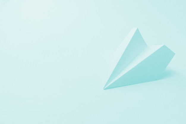 Aereo di carta su uno sfondo blu pallido.