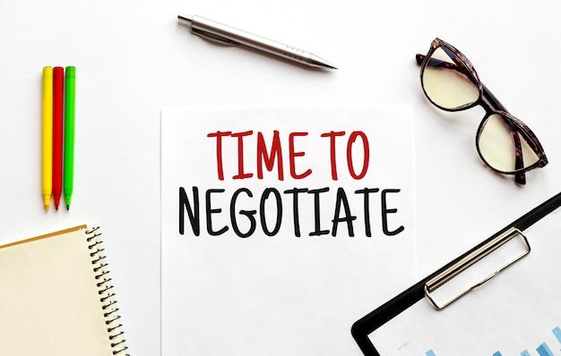 Piatto di carta, bicchieri, blocco note e testo time to negoziate