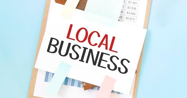 Piatto di carta con testo aziendale locale. diagramma, blocco note e sfondo blu