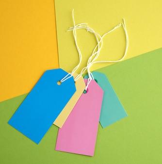 Etichette rettangolari di carta su una corda su uno sfondo colorato
