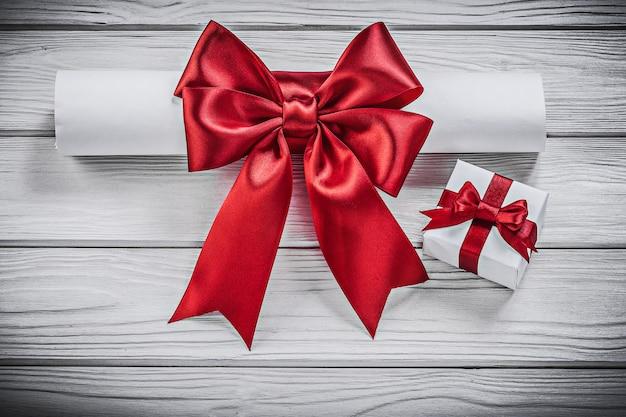 Rotolo di carta con concetto di vacanze di scatola regalo fiocco rosso