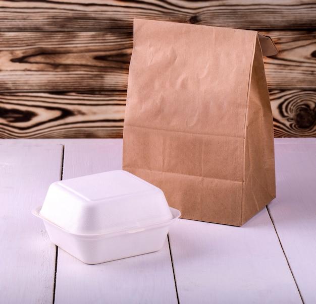 Sacchetto della spesa e contenitore di carta per la colazione sul tavolo di legno bianco