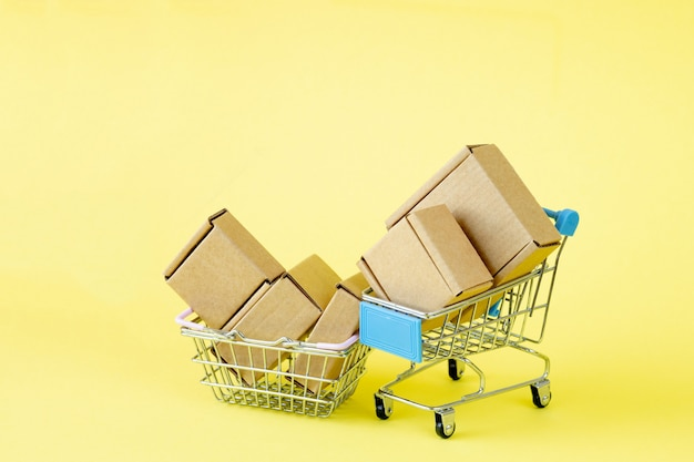 Sacchetti della spesa di carta in un carrello della spesa su colore giallo