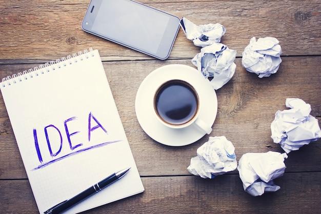 Carta, smartphone, penna e tazza di caffè sulla scrivania in legno
