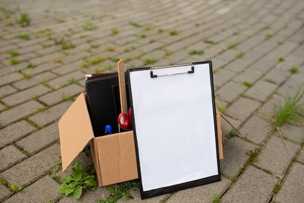 Tavoletta di carta con una scatola e articoli di cancelleria su ciottoli.