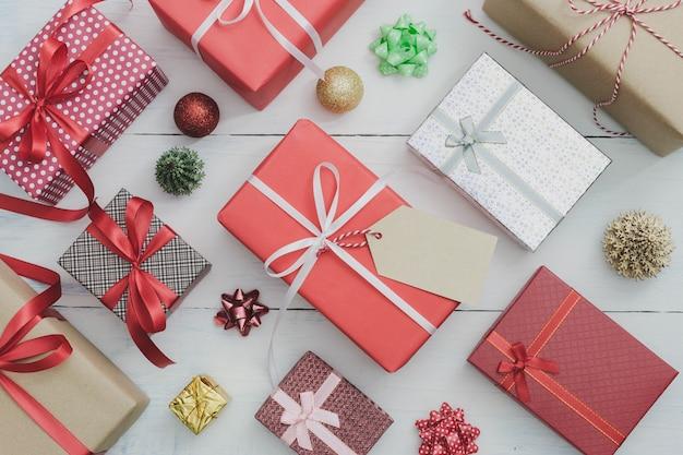 Etichetta di carta con il contenitore di regalo di feste del nuovo anno e di natale con l'ornamento decorativo sulla tavola di legno bianca. concetto di congratulazioni e di giri.