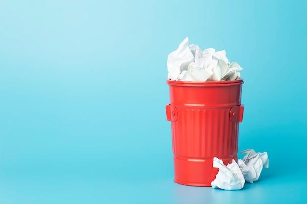 Cestino di carta e rifiuti in un cestino della spazzatura su sfondo blu. rifiuti e raccolta differenziata e concetto di riciclaggio