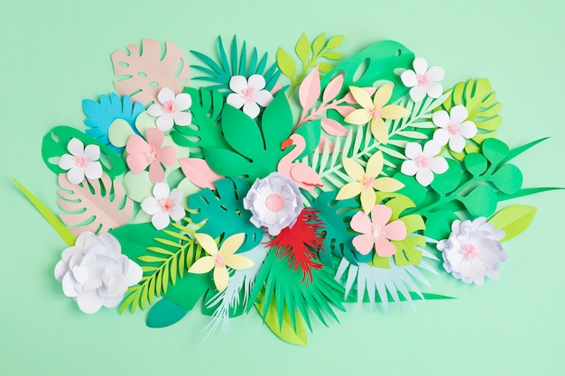 Foglie e fiori tropicali di carta sopra la parete pastello. vacanze esotiche estive, idea progetto fai da te. vista dall'alto laici piatta