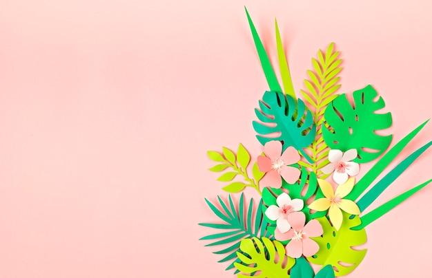 Foglie e fiori tropicali di carta sulla parete pastello rosa. vacanze esotiche estive, vista dall'alto laici piatta