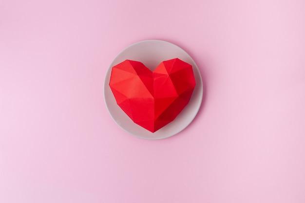 Cuore del volume di carta sul piatto su superficie rosa con spazio vuoto