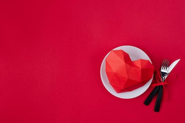 Cuore del volume di carta sul piatto su superficie rossa con spazio vuoto