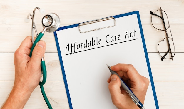 Carta con aca affordable care act sul tavolo dell'ufficio e sullo stetoscopio.