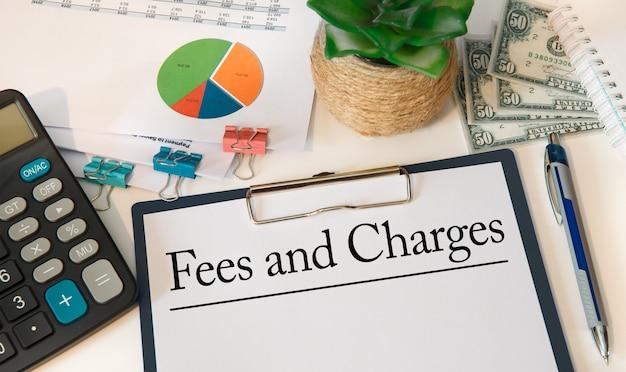 Carta con commissioni e addebiti sul tavolo dell'ufficio, calcolatrice e denaro