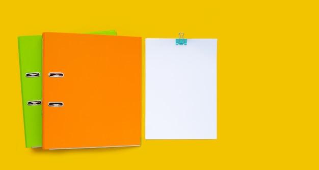Carta con cartelle per ufficio su sfondo giallo.