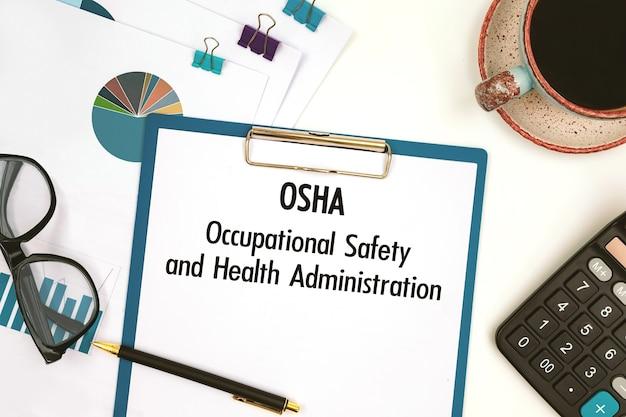 Carta con testo osha occupational safety and health administration sul tavolo dell'ufficio, calcolatrice e tazza di caffè