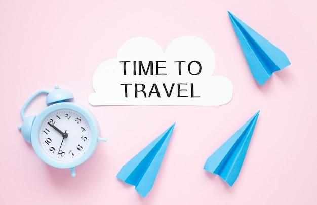 Carta con testo time to travel con orologio e aeroplano di carta su un tavolo rosa.