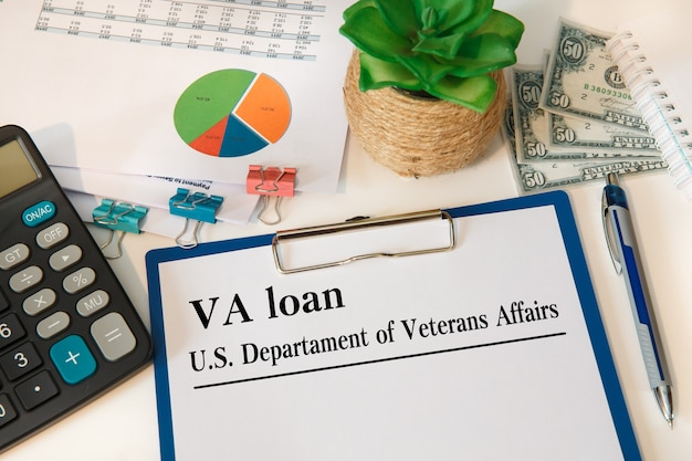Documento con prestito va - us department of veterans affairs sul tavolo, calcolatrice e bicchieri