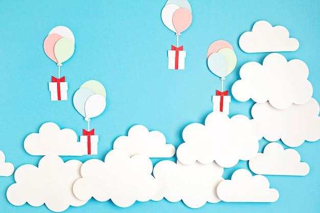 Palloncini papercut e confezione regalo galleggianti nel cielo blu con nuvole