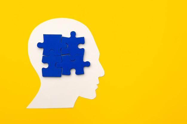 Papercut silhouette testa con pezzi di un puzzle su sfondo giallo