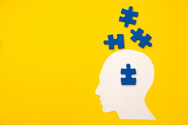 Sagoma testa papercut con pezzi di un puzzle sulla superficie gialla