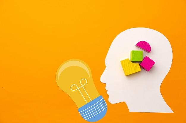 Sagoma di testa papercut con pezzi di costruttore di giocattoli su sfondo giallo