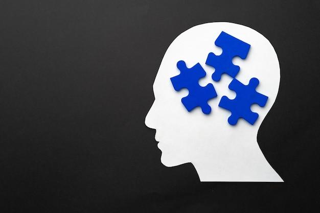 Testa papercut con pezzi di un puzzle su sfondo nero