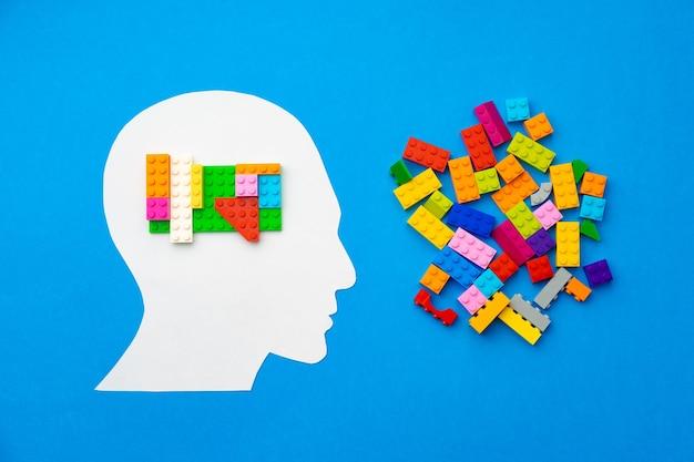 Sagoma di papercut della testa umana con pezzi colorati del costruttore