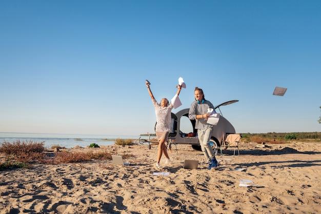 Documenti via. una coppia di liberi professionisti si sente pazza mentre butta via tutte le carte all'inizio del loro viaggio