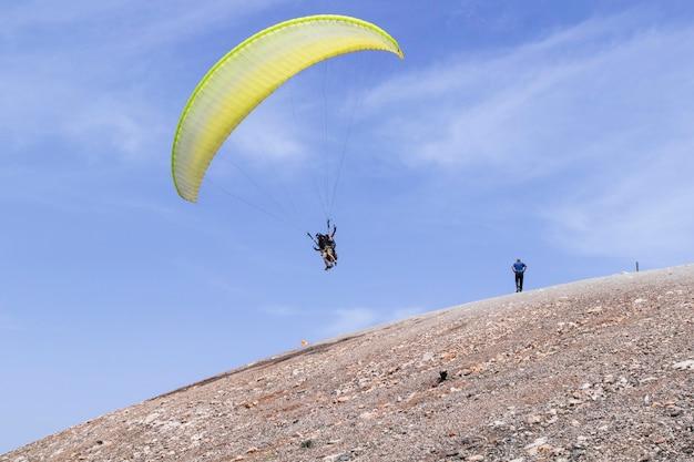 Paracadute con persone che volano nel cielo blu dalla montagna