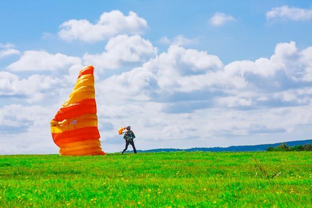 Il paracadutista è atterrato su un campo erboso. paracadutismo. paracadutismo.