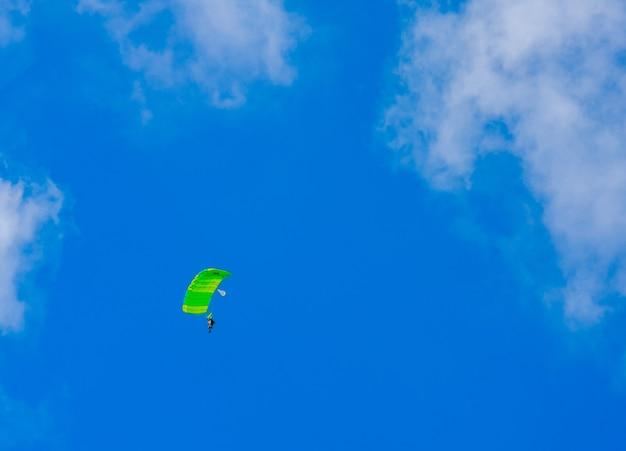 Un paracadutista con un baldacchino verde chiaro contro uno sfondo di cielo azzurro e nuvole bianche. paracadutismo.