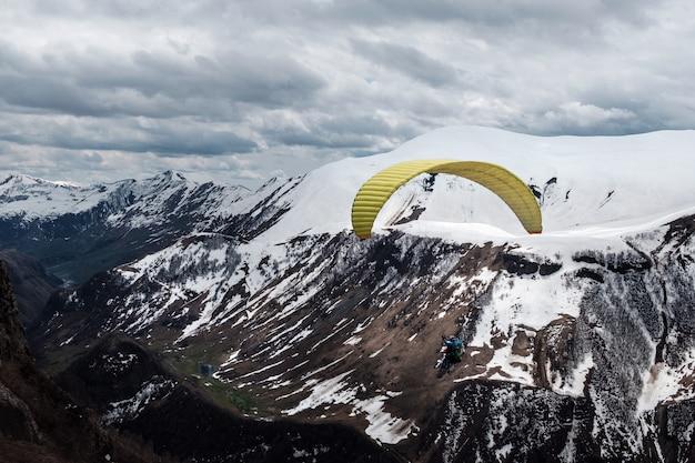 Parapendio in aria sopra le montagne