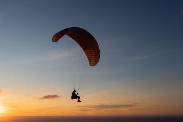 Aliante che sorvola la riva di mare al tramonto. sport in parapendio