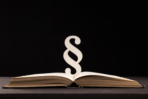 Segno di paragrafo e libro aperto su sfondo di pietra nera