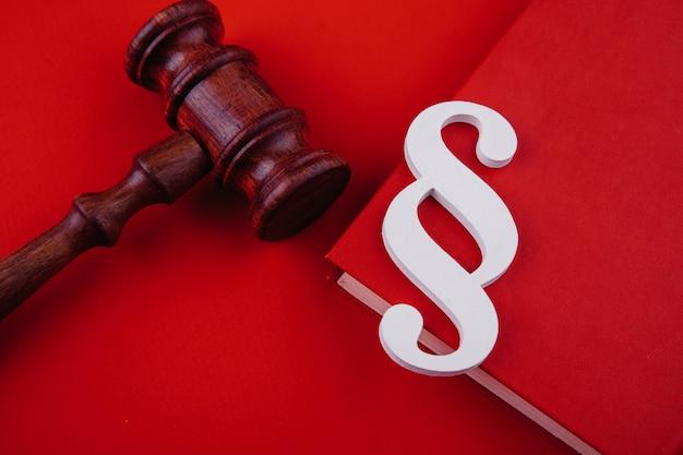 Il simbolo del paragrafo è su un libro e un martelletto su sfondo rosso concetto di legge e giustizia