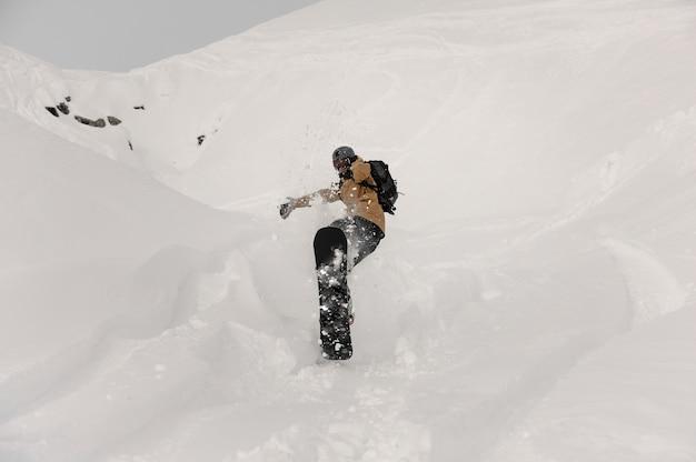 Snowboarder paralimpico facendo un trucco di salto sulla collina coperta di neve bianca nella famosa località turistica di gudauri in georgia
