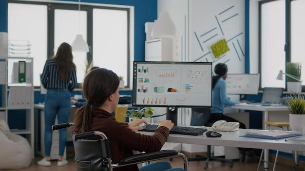 Esperto finanziario paralizzato seduto su una sedia a rotelle che analizza le statistiche economiche dell'azienda in ufficio commerciale digitando sul computer