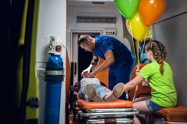 Un paramedico in uniforme medica blu regola una maschera di ossigeno su una donna sdraiata su una barella.