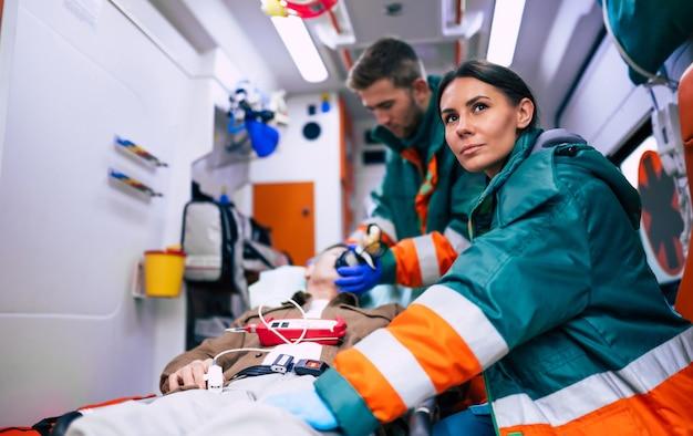 I paramedici stanno lavorando con un paziente anziano mentre giace su una barella in un'ambulanza.