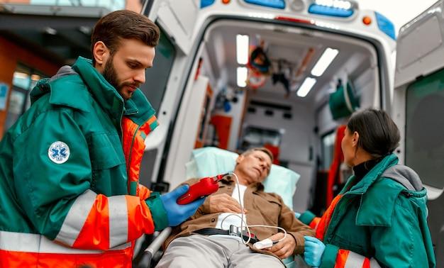 I paramedici controllano il livello di ossigeno nel sangue e trasportano la barella del paziente anziano dalla moderna ambulanza per ulteriori cure mediche presso la clinica.