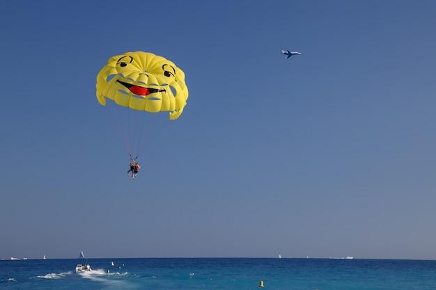 Paracadute ascensionale sulla spiaggia faccina sorridente viaggiatori con paracadute che si divertono ad attività sportive estreme