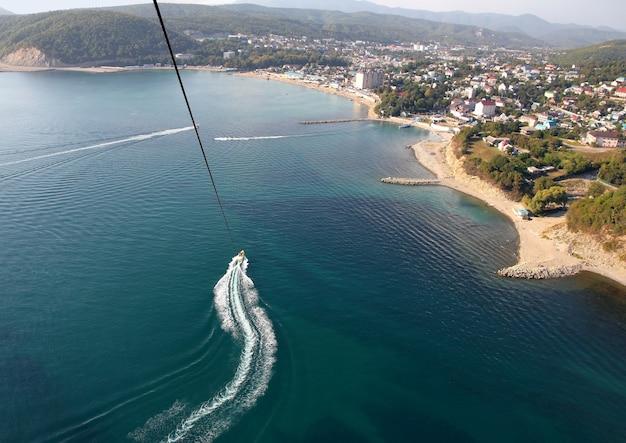 Parasailing sopra l'acqua vicino alla costa della città di dzhubga
