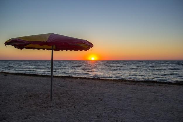 Ombrellone in riva al mare ad alba con cielo colorato all'orizzonte.