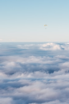 Paracadutista che vola sopra le nuvole