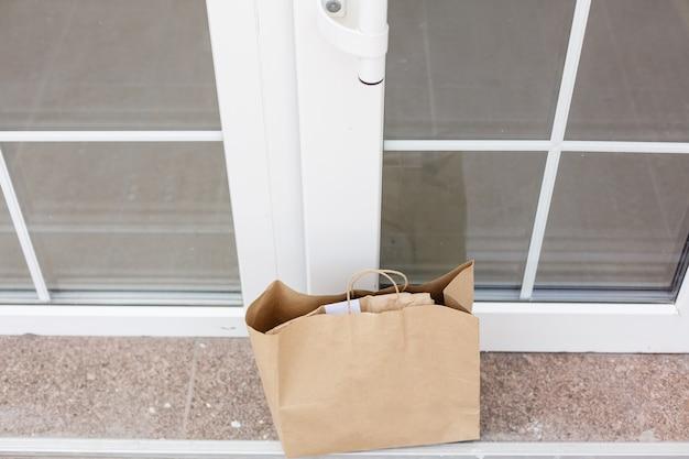 Scatola di cartone per pacchi nella porta d'ingresso. consegna porta a porta di merce buona durante la quarantena, consegna fuori porta, acquisto di e-commerce durante il blocco del covid-19, concetto di distanza sociale.