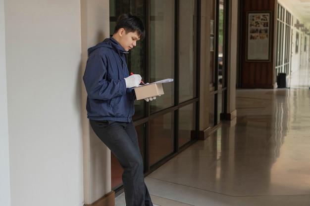 Concetto di consegna del pacco il postino con la giacca blu che controlla l'elenco e il prossimo posto dove andare per consegnare il pacco.