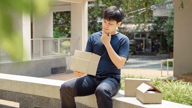 Concetto di consegna dei pacchi il giovane che sembra deluso dalle cose nella scatola di cartone che non è la stessa di quello che ha visto nella foto.