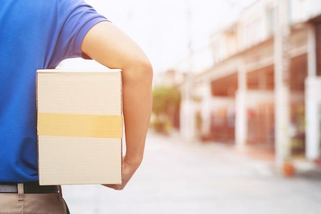Addetto alla consegna pacchi di un pacco tramite un servizio di invio a domicilio. consegna a mano cliente di presentazione che accetta una consegna di scatole dal fattorino.