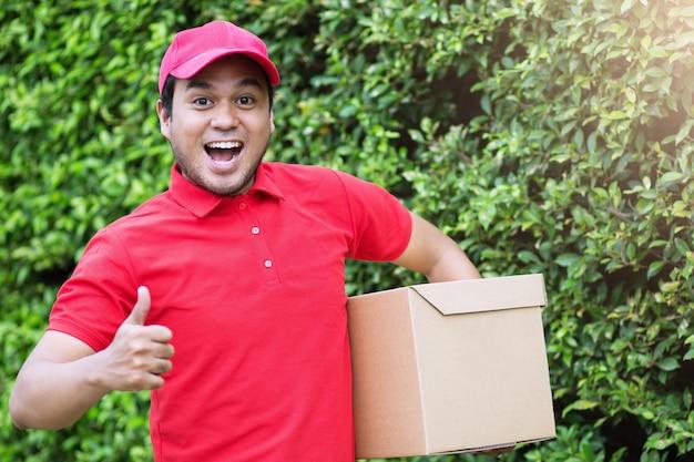 Uomo di consegna del pacco corriere postale sorridente accanto al furgone del carico che consegna il pacchetto. servizio impressionante.